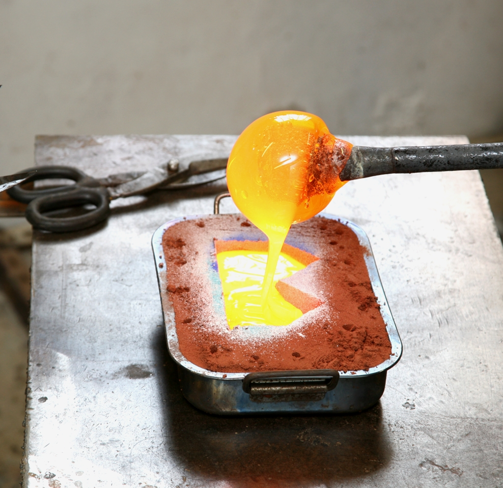 Filling the sand mould with molten glass